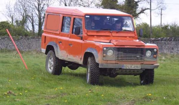 An Orange defender driving through yellow sticks during a driver improvement course for professionals and corporates.