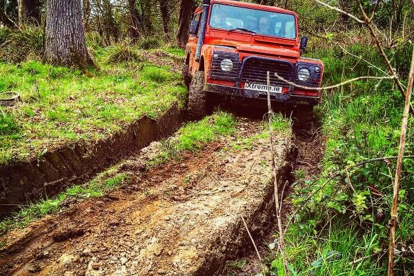 Orange land rover defender driving through a 4x4 dirt track, which is part of the advanced driving course.