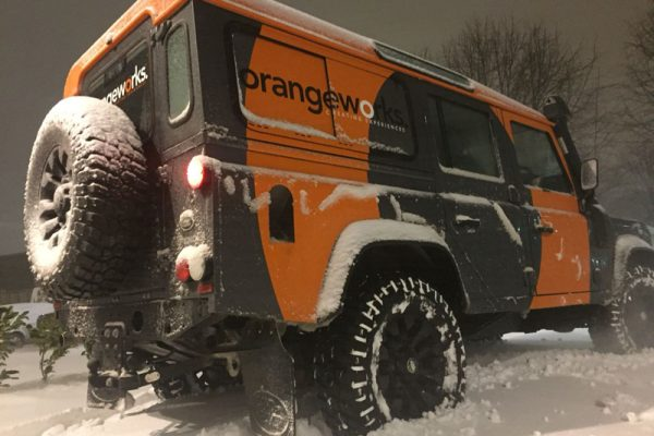 An Orangeworks vehicle parked in the snow waiting to show delegates how to drive safe and in adverse driving conditions.