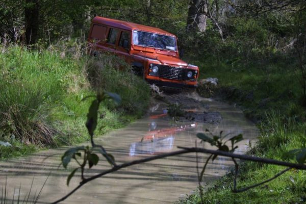 Orangeworks Landrover Defender driving through water during one of the advanced weather conditions driver training course.